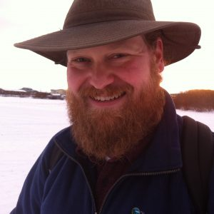 smiling bearded man in hat outside in winter